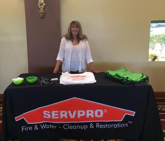 Lady standing behind table with SERVPRO tablecloth.  Giveaways on top of table